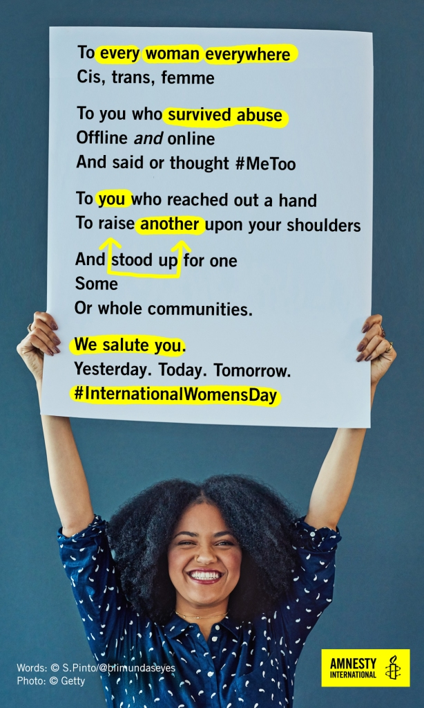 International Women's Day 2018, image of a woman of colour grinning and holding up a poster with the words of a solidarity poem by S. Pinto.